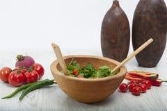 De madera en el piso, de madera en ensalada verde, tomate y pimienta Fotos de archivo libres de regalías