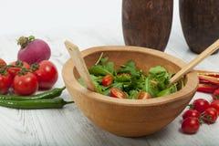 De madera en el piso, de madera en ensalada verde, tomate y pimienta Foto de archivo