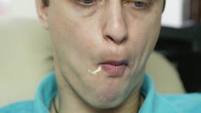 De magere mens eet snel voedselsnack met groot plezier kerel het kauwen ongezonde kost met grote eetlust Langzame Motie stock video