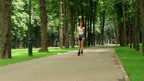 De magere vrouwen in borrels berijdt op rollen in een park stock footage