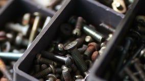 De magneet trekt ijzerbouten van diverse hardwarebevestigingsmiddelen aan, noten, bouten, schroeven, in doos stock footage