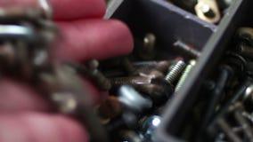 De magneet trekt ijzerbouten van diverse hardwarebevestigingsmiddelen aan, noten, bouten, schroeven, in doos stock video