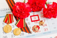 9 de maio cartão festivo com as medalhas do jubileu da grande guerra patriótica, de cravos vermelhos e de fita de St George Fotos de Stock Royalty Free