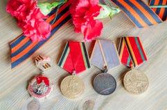 9 de maio composição festiva - medalhas do jubileu da grande guerra patriótica com os cravos e a fita vermelhos de St George Fotografia de Stock