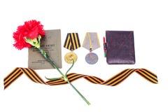 9 de maio fundo com as medalhas da grande guerra patriótica, de cravos vermelhos e de fita de George Fotografia de Stock Royalty Free