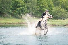 20 de maio de 2018 moscow Uma força das amazonas vadeando o rio montado em cavalos Foto de Stock