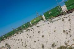 25 de maio de 2017 - o trem de mercadorias com os recipientes de carga verdes enrola sua maneira com a paisagem de Nevada Infinid Fotos de Stock Royalty Free