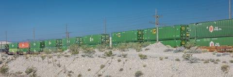 25 de maio de 2017 - o trem de mercadorias com os recipientes de carga verdes enrola sua maneira com a paisagem de Nevada Linha e Imagens de Stock