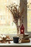 De maison toujours la vie confortable : chandelier et livres sur le rebord de fenêtre contre le paysage dehors Vacances d'automne Photographie stock
