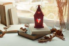 De maison toujours la vie confortable : chandelier et livres sur le rebord de fenêtre contre le paysage dehors Vacances d'automne Photo libre de droits