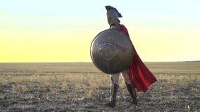 De majestueuze Roman legionair met een schild in zijn hand bevindt zich op het gebied terwijl in de wind zijn rode mantel is stock videobeelden