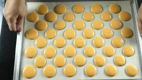 De makarons drukken gebakjeroom of deeg op de vorm op een bakseldienblad royalty-vrije stock afbeelding