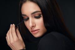 De Make-up van de schoonheid Vrouw met Lange Zwarte Wimpers en Mascaraborstel stock fotografie