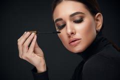 De Make-up van de schoonheid Vrouw met Lange Zwarte Wimpers en Mascaraborstel stock afbeeldingen