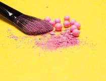 De make-upborstel met verpletterde en gehele flikkering bloost ballen stock foto