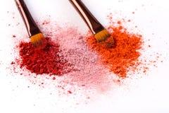 De make-upborstels met blozen of oogschaduw van roze, rood en koraaltonen op witte achtergrond wordt bestrooid die royalty-vrije stock fotografie