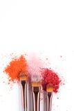 De make-upborstels met blozen of oogschaduw van roze, rood en koraaltonen op witte achtergrond wordt bestrooid die stock foto