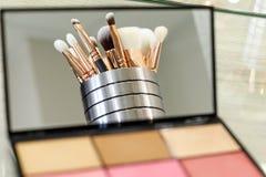 De make-upborstels worden weerspiegeld in een paletspiegel met schaduwen royalty-vrije stock fotografie