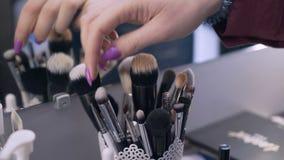 De make-upborstels zijn in een opslagkop de vrouwelijke hand met purpere spijkers plukt een borstel en trekt het uit de kop 4K stock footage