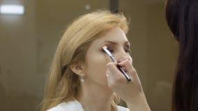 De make-upkunstenaar bereidt volwassen vrouw aan het stadium voor, make-upruimte stock footage