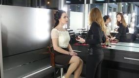 De make-upkunstenaar doet een make-up aan donker-haired meisje stock footage