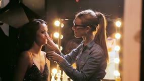 De make-upkunstenaar helpt actrice voor show bij spiegel voorbereidingen treffen stock video
