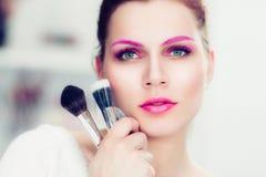 De make-upkunstenaar houdt poederborstels Stock Foto's