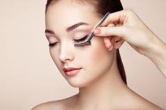De make-upkunstenaar lijmt wimpers royalty-vrije stock afbeeldingen