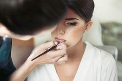De make-upkunstenaar maakt jonge mooie bruid royalty-vrije stock foto's