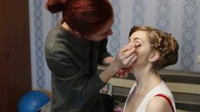 De make-upkunstenaar maakt mooie vrouw met kapsel goed stock videobeelden