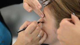 De make-upkunstenaar maakt de make-up van het modellenoog stock video
