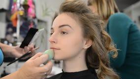 De make-upkunstenaar maakt de make-up van het modellenoog stock videobeelden
