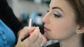 De make-upkunstenaar maakt de make-up van modellenlippen stock videobeelden