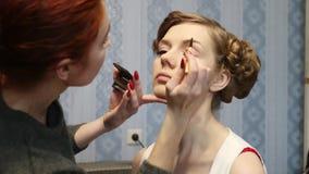 De make-upkunstenaar maakt vrouw met kapsel in ruimte goed stock footage