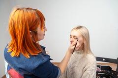 De make-upkunstenaar met rood haar legt samenstelling aan gesloten ogen met een borstel op toepast schaduwen op de oogleden in de royalty-vrije stock foto