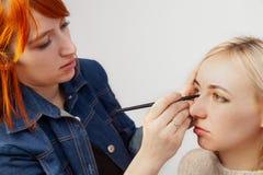 De make-upkunstenaar met rood haar legt samenstelling aan gesloten ogen met een borstel op toepast schaduwen op de oogleden in de stock foto's