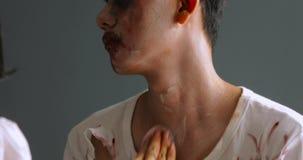 De make-upkunstenaar past Halloween-make-up op de mens toe stock video