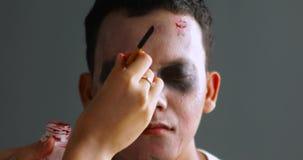 De make-upkunstenaar past Halloween-make-up toe stock videobeelden
