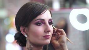 De make-upkunstenaar past make-up op een aantrekkelijk jong model voor fotozitting toe stock videobeelden