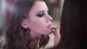De make-upkunstenaar past make-up op een aantrekkelijk jong model voor fotozitting toe Lippen en ogen stock videobeelden