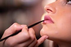 De make-upkunstenaar past roze toe polijst lippenstift Mooi vrouwengezicht Hand van samenstellingsmeester, het schilderen lippen  royalty-vrije stock foto