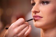 De make-upkunstenaar past roze toe polijst lippenstift Mooi vrouwengezicht Hand van samenstellingsmeester, het schilderen lippen  stock afbeelding
