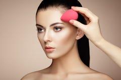 De make-upkunstenaar past skintone toe royalty-vrije stock afbeelding