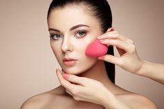 De make-upkunstenaar past skintone toe Stock Foto