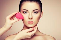 De make-upkunstenaar past skintone toe Stock Afbeeldingen