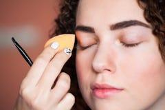 De make-upkunstenaar past skintone toe Van de kunstenaarsBeautiful van de sponsmake-up de vrouwengezicht Skincarestichting stock afbeelding