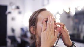 De make-upkunstenaar past stichting van een mooi jong meisje in de make-upstudio gebruikend toe vingers en borstel Sluit omhoog stock videobeelden