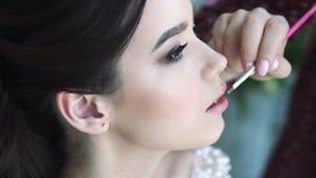 De make-upkunstenaar schildert de lippen van een jong mooi meisje stock video