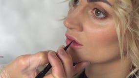 De make-upkunstenaar schildert de lippen van een jonge vrouw in een schoonheidssalon stock videobeelden