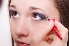 De make-upkunstenaar schildert de ogen van een model Stock Fotografie
